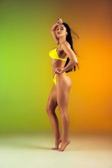 グラデーションの壁にスタイリッシュな黄色の豪華な水着で若いフィット感とスポーティーな女性のファッションの肖像画