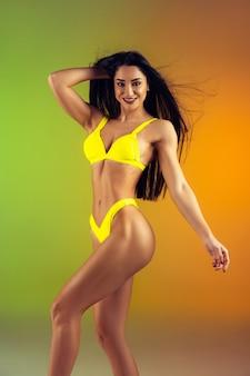 그라데이션 벽에 세련된 노란색 고급 수영복을 입은 젊고 스포티한 여성의 패션 초상화