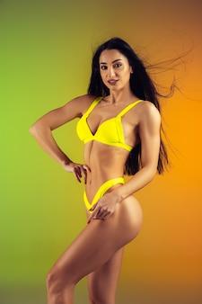 スタイリッシュな黄色の豪華な水着で若いフィットと陽気な女性のファッションの肖像画。夏にぴったりのパーフェクトボディ。