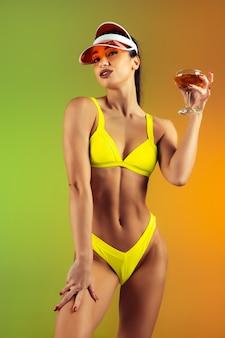 夏の準備ができてグラデーションの壁にスタイリッシュな黄色の豪華な水着でカクテルと若いフィット感とスポーティーな女性のファッションの肖像画