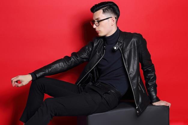 若いハンサムな男のファッションの肖像画。黒革のジャケット、タートルネック、メガネ、ブルネットの髪、赤い背景