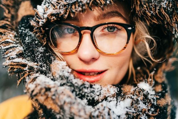 Фасонируйте портрет молодой счастливой девушки в стеклах, обернутых в коричневом шарфе покрытом снегом