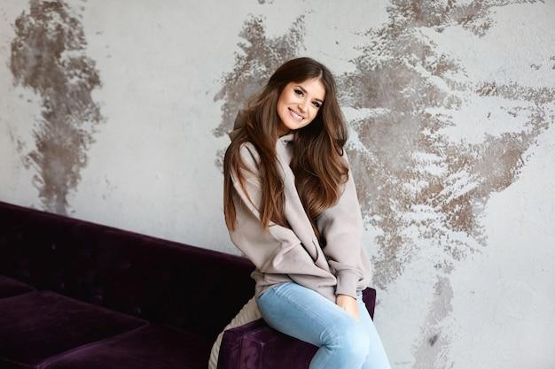灰色のパーカーを屋内で流行に敏感な若い女性のファッションの肖像画