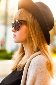 日没時のビーチで、帽子とサングラスをかけた若い流行に敏感な女性のファッションの肖像画、レトロなスタイルの色調寒い季節。暖かい服。