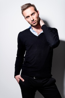 黒のプルオーバーとコントラストの影と青いシャツの若い男のファッションの肖像画。