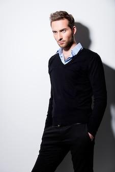 黒のプルオーバーとコントラストの影と青いシャツの若い男のファッションの肖像画