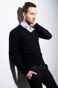 대비 그림자가있는 검은 색 풀오버와 파란색 셔츠에 젊은 남자의 패션 초상화