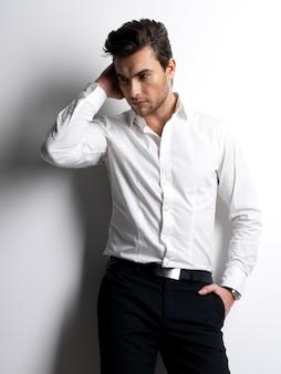 白いシャツを着た若い男のファッションの肖像画は、コントラストの影で壁を越えてポーズをとる