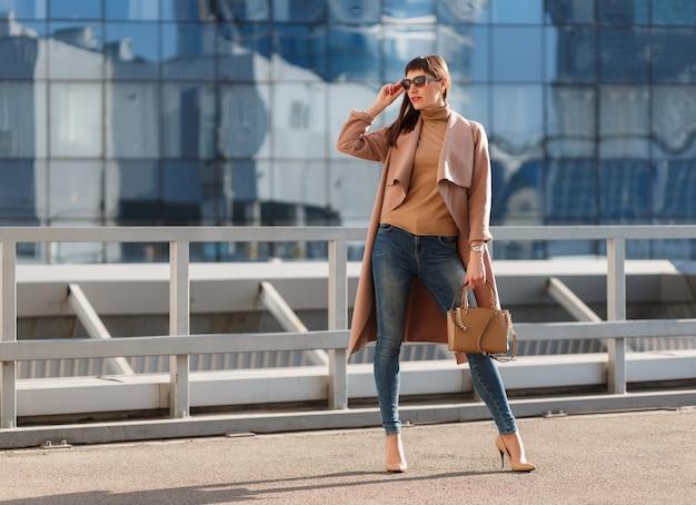 도시 배경에 멋진 갈색 베이지색 코트, 데님 청바지, 선글라스를 쓴 젊은 모델 여성의 패션 초상화.
