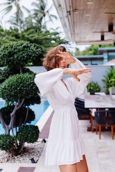 흰색 빛 여름 드레스와 럭셔리 풍부한 빌라에서 큰 검은 거대한 부츠에 젊은 꽤 세련된 여자의 패션 초상화