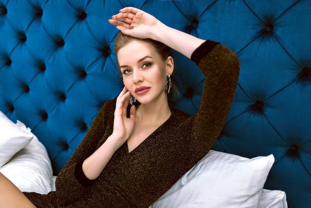 Фасонируйте портрет молодой чувственной элегантной женщины, носящей вечернее модное платье и украшения, лежа на кровати, позируя в роскошном отеле, мягких тонах.