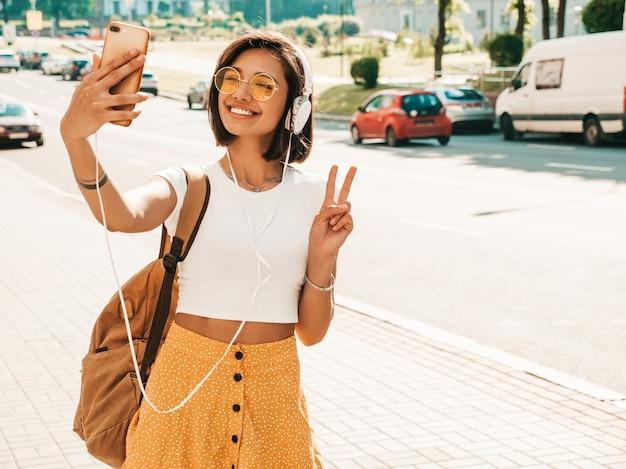Фасонируйте портрет молодой стильной женщины битника идя на улицу. девушка делая selfie. улыбаясь модель наслаждается ее выходными с рюкзаком. женщина слушает музыку через наушники