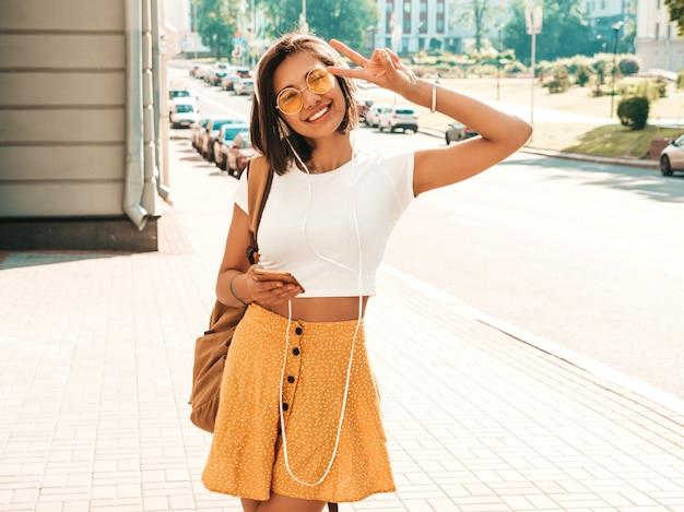 Фасонируйте портрет молодой стильной женщины битника идя на улицу. девушка нося милый ультрамодный обмундирование. улыбчивая модель наслаждается ее выходными, путешествует с рюкзаком. женщина слушает музыку через наушники