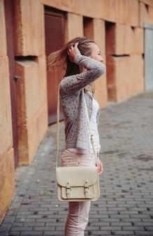屋外で彼女の髪に触れる上に灰色のジャケット、ピンクのジーンズ、白いサッチェルバッグを身に着けている若いトレンディな女性のファッションの肖像画