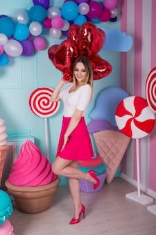 気球、カラフルな背景にキャンディーとピンクのドレスを着た若い女性のファッションの肖像画。