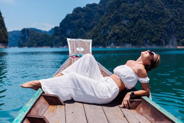 セーリングタイの木製ボートで、休暇中の白いトップとパンツの若い女性のファッションの肖像画。旅行のコンセプト。カオソック国立公園の女性。
