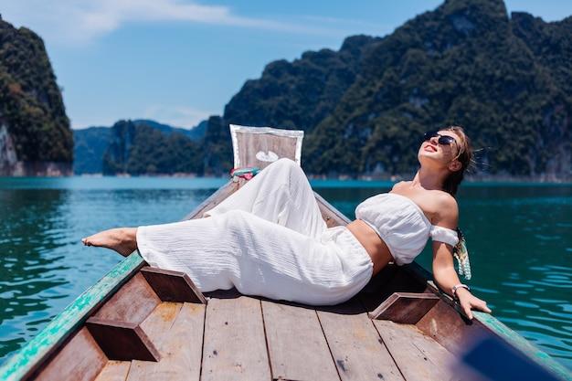 Фасонируйте портрет молодой женщины в белой верхней части и штанах на отдыхе, на тайской деревянной лодке плавания. концепция путешествия. самка в национальном парке као сок.