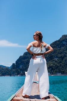 흰색 상단과 휴가, 태국 나무 보트 항해에 바지에 젊은 여자의 패션 초상화. 여행 개념. 카오 속 국립 공원의 여성.