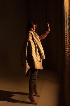 灰色のコートを着て、部屋でポーズをとって若い女性のファッションの肖像画。