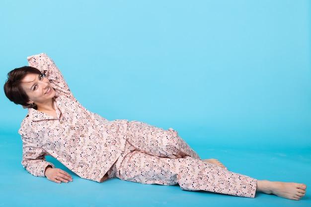 Модный портрет довольно крутой женщины в домашней пижаме с удовольствием над синей стеной