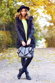 Fashion portrait of pretty young blonde smiling woman wearing trendy coat, vintage hat and neon sweater, posing at countryside park in nice sunny fall autumn day.