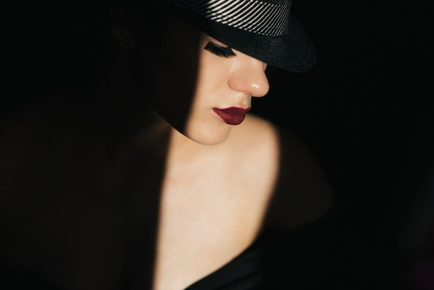 Fashion portrait in profile of a young sexy girl in a black hat with red lipstick