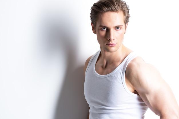 Moda ritratto di giovane uomo sexy in camicia bianca pone sul muro con ombre di contrasto.