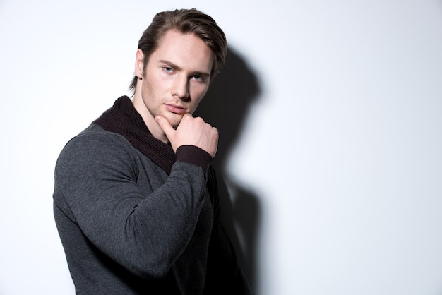 Fashion portrait of sexy young man with hand near face  in casual poses over wall with contrast shadows.