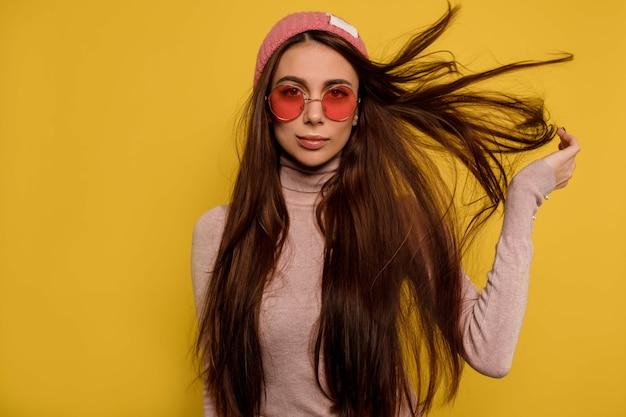 Moda ritratto di ragazza appariscente con capelli volanti che indossa occhiali rotondi rosa e berretto
