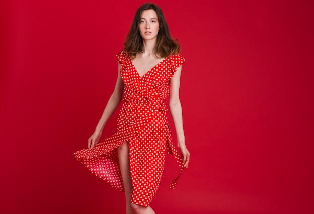 Moda ritratto di giovane donna sorridente in abito rosso punteggiato su rosso