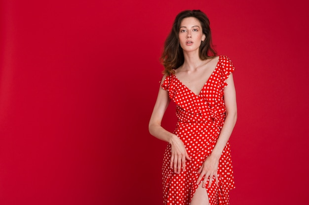 Fashion portrait of smiling young woman in red dotted dress on red