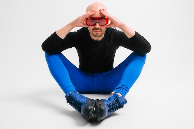 Fashion portrait of stylish bald man in blue joggers and indigo boots looking at camera over white wall.