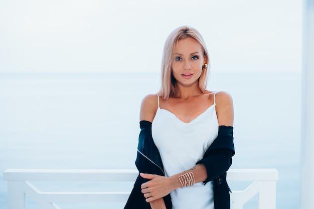 Fashion portrait of stylish caucasian woman in silk long dress black blazer in luxury place with sea views