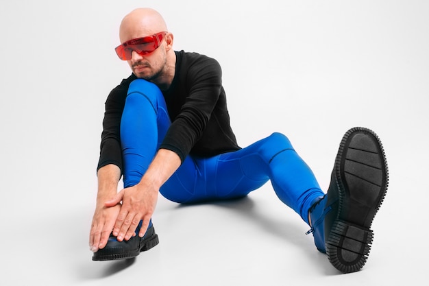 Fashion portrait of stylish man in blue tights and blue boots stretching and exercising.