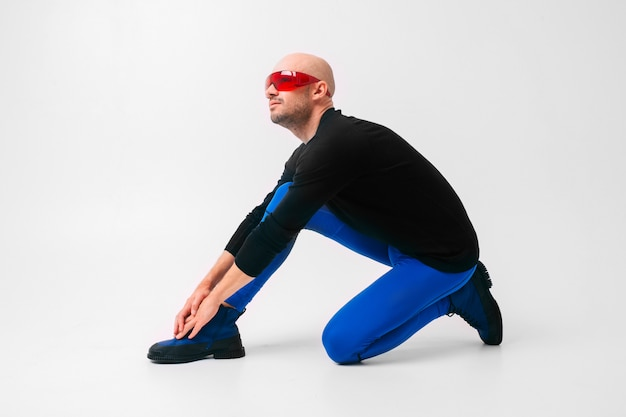 Fashion portrait of stylish man in blue tights and boots stretching and exercising over white studio wall.
