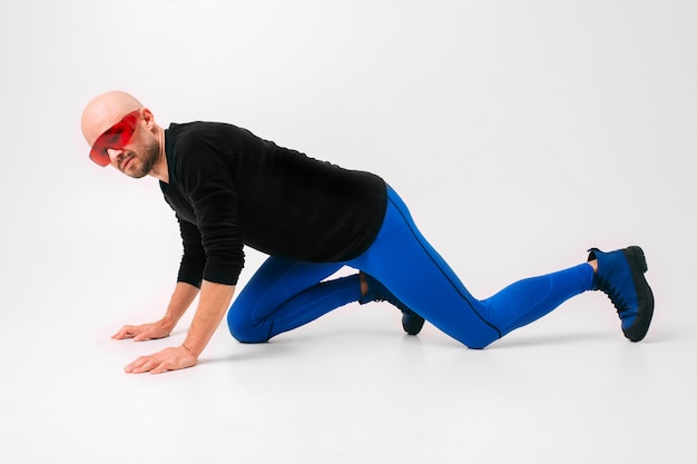 Fashion portrait of stylish man in blue tights and boots stretching and exercising.