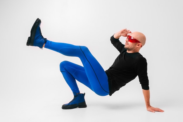Fashion portrait of stylish man in red glasses, blue tights and  boots stretching and exercising.