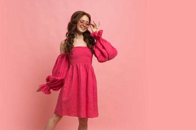 Fashion portrait of stylish red-haired woman posing in pink lien dress with sleeves over pink wall. full lenght.