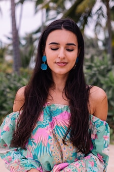 Fashion portrait of stylish woman in colorful print long sleeve top and pink shorts on beach, tropical background.