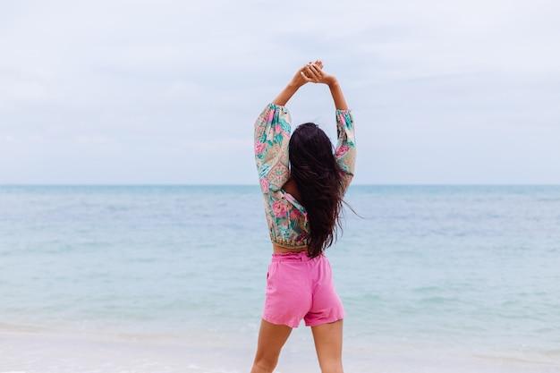 Moda ritratto di donna alla moda in top a maniche lunghe con stampa colorata e pantaloncini rosa sulla spiaggia, sfondo tropicale.