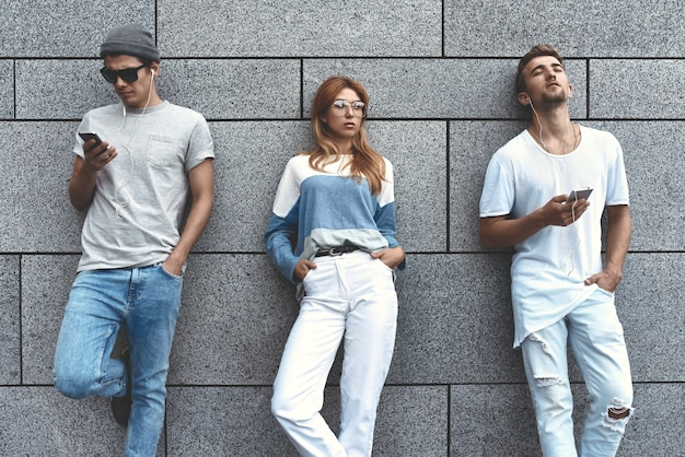 Fashion portrait of three best friends posing at street, wearing stylish outfit and denim against gray wall .