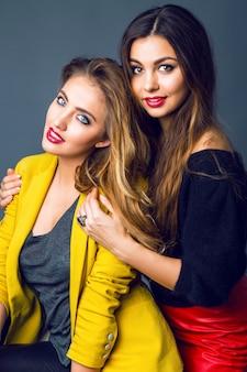 Adatti il ritratto di due incredibili belle donne bionde e castane, che indossano trucco fumoso luminoso e vestiti casual eleganti alla moda.
