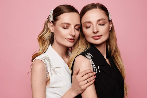 Fashion portrait of two beautiful young twins model girls with trendy makeup isolated at pink background. beauty portrait of twins women with fashionable accessories, perfect makeup, and smooth skin