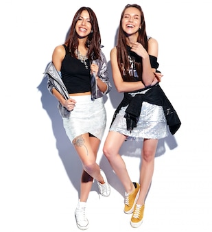 Fashion portrait of two smiling brunette models in summer casual hipster clothes isolated on white. full length