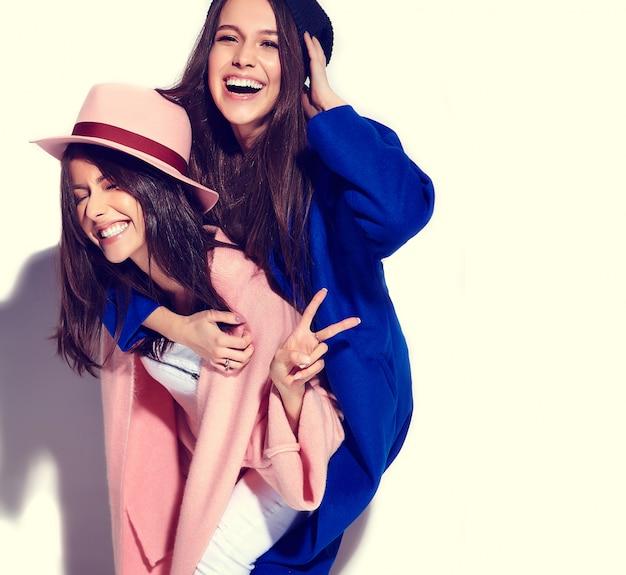 Ritratto di moda di due modelli sorridenti delle donne del brunette in cappotto casuale dei pantaloni a vita bassa di estate isolato su bianco. ragazze che si tengono sulla schiena
