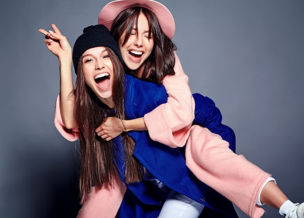 Fashion portrait of two smiling brunette women models in summer casual hipster overcoat posing . girls holding each other on back