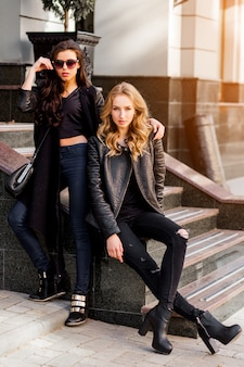 Fashion portrait of two stylish pretty women posing on the street in sunny day. wearing trendy urban outfit , leather jacket and boots heels. young friends  waiting on stairs outdoor.