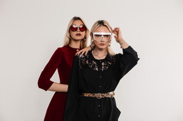 Модный портрет двух подружек-подростков в модных цветных молодежных солнцезащитных очках в красно-черных платьях возле серой винтажной стены