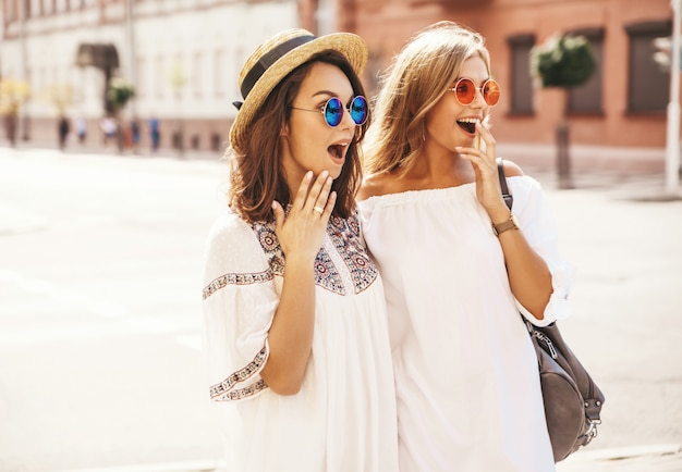 Fashion portrait of two young stylish hippie brunette and blond women models. best friends in white summer hipster dress posing