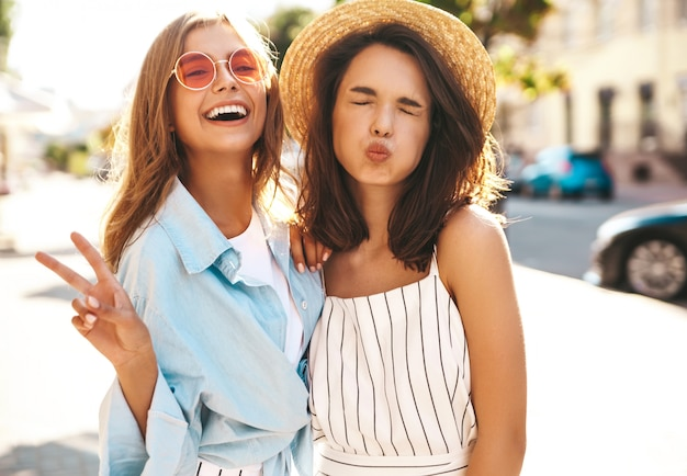 Fashion portrait of two young stylish hippie brunette and blond women models in summer sunny day in hipster clothes posing on the street background. no makeup